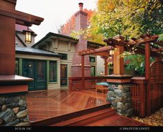 Craftsman Style  a unique deck and pergola featuring cedar beams and stone piers built to match the home's original stone foundation