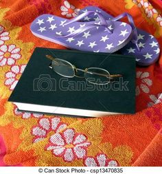 A book, reading glasses, sandals and a towel stand ready for a trip to the beach.
