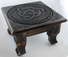 Providing either a portable altar space or a raised platform for elements within your sacred space, this altar table is a wonderful tool both for those seeking a space that they can conceal as well as for those who wish to enhance their more permanent altars. Hand carved of wood and antiqued to provide a dusky, aged appearance, this table is a wonderful display of craftsmanship. Its four solid legs are beautifully crafted to lend stability upon most surfaces while creating the impressi…