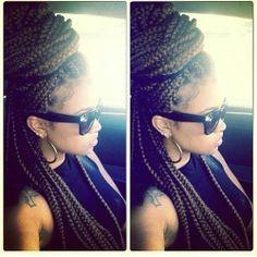 Dark brown box braids in a bun.