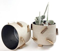 Hand sculpted stoneware planters. The outside is left unglazed exposing a sandy textured clay body with dimensional gold luster glazed thin rectangular shapes a