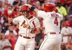 Yadier Molina congratulates teammate Tony Cruz on his three-run home run during the second inning of a baseball game against the Cincinnati Reds. Cards won 8-4. 9-20-14