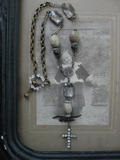 created by Redbird ~ vintage brass chain and gorgeous Art Deco crystal bezels connect with antique wooden beads, rhinestone connectors and rosary center to dangle an ancient primitive metal bird from Europe and lucious antique paste cross from France. Length to 13 inches, cross measuring 1 and 1/4th inches, antique brass and rhinestone closure.    i find shelter in the shadow of your wings ...