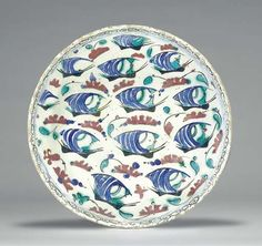 AN IZNIK POTTERY DISH  OTTOMAN TURKEY, CIRCA 1600  With rounded edge on short foot, the white interior painted with five rows of sailing vessels with blue striped sails, various green and red motifs scattered in the sea, with thin border of black spirals, the exterior with alternating blue spiral and trefoil motif, rim fritted, glaze   11 7/8in. (30cm.) diam.