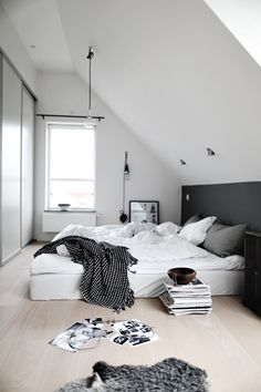white & grey bedroom with a slanted ceiling. GORGEOUS. love the bed right on the floor. comfy.