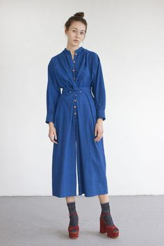 """PLEASE ALLOW 1-2 WEEKS BEFORE SHIPPING.ORIGINAL PRICE: 280 euros.DISCOUNTED PRICE: 196 euros.- 100% washed indigo cotton from Japan.- Jumpsuit with wooden button fastenings through front. - Stand collar.- Long sleeves.- Front is designed to be crossed/tied up in the back.- Wide, pleated aikido-style culotte pants.- Hidden side pockets.- Made in Barcelona, Spain.The model is 176cm (5 ft. 9) tall and wears a size S.Size guide:- XS: Bust: 82cm (32.3""""), Waist: 62cm (24.4""""), Hips: 90cm ..."""