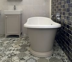 A painted boat bath with matching basin stand works perfectly with the patterned tiles