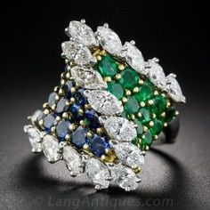 A fabulous work of jewelry sculpture from mid-century France, masterfully hand fabricated in platinum and 18K yellow gold. The dynamic French twist is crowned with a zig-zag of sparkling white marquise diamonds set atop a bifurcated base studded with bright green round emeralds on one side and deep blue sapphires on the other. The size 5 3/4 ring shank cleverly opens like a miniature hinged bangle bracelet, so sizing may be a bit limited. Magnifique!
