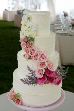 Four-tiered white cake adorned with a cascade of roses and ranunculi | Photo by Jen Osojnicki