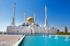 The multi-domed Nur-Astana Mosque in Astana, Kazakhstan has a magnificent gold dome and a fountain at the front of the building