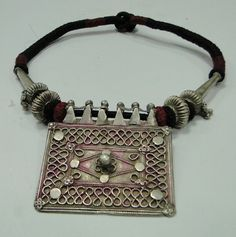 India   Old silver house amulet pendant (A symbol of family unit represented by a walled-in rectangle, the amulet uses stamped floral units to cover joins)    strung on yarn with silver beads.
