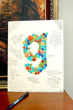 Button collage with messages from the attendees to the mother and baby :) Used foam core board, hot glue, and a good pen. Oh, and buttons. Be sure to use a size that is easy to frame or have it framed for the guest of honor.