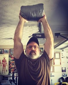 Sandbag overhead press.  I use field expedient, homemade, sandbags instead of the high speed, brand name ones, with handles.  My sandbags have no handles, are difficult to grip, can be made with little cost, last forever, and are capable of kicking your butt, in a variety of ways.  They are great for most types of training.   Grab a sandbag and try it out.   #fit #strength #conditioning #fitness #sandbag #exercise #martialarts #sports #athlete #military #dempseysresolutionfitness