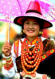 Tibetan Woman from Ngaba / Ngawa in traditional Tibetan region of Amdo, Tibet (it is now known as Aba and now demarked by the Chinese into Sichuan province). She wears lovely coral necklaces, in Amdo the fashion is to have neatly arrange necklaces with no crossing. This contrasts with regions like Yushu in Kham where men and women often wear crossing, even tangles necklaces. Her earrings are 24k gold, her belt is specific to Amdo regions like Ngawa and Golok. Photo by Ge Jialin (葛加林)