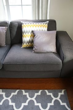 New Years Home Decor Update: Easy DIY Throw Pillow Makeover. Click to see more photos and instructions on this easy home décor refresh on fabeveryday.com.  Gray and white throw pillows with yellow accent color. Gray and white quatrefoil rug from Target, and dark gray Ikea Kivik sofas.