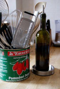 Lege blikken van tomaten zijn perfect voor het opbergen van keukengerei. lege flessen bewaar ik voor pikante olie.