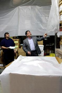 Deptartment of Corrections administrator of logistics Jon Hanson touches the tarp protecting prisoner medical records as warehouse supervisor Jason Newton looks on at the warehouse across the street from the prison. Records Management, Run Out, When It Rains, Prisoner, Warehouse, Medical, Street, Medicine, Magazine
