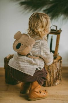 child crouching in beige sweater and brown leather boots.
