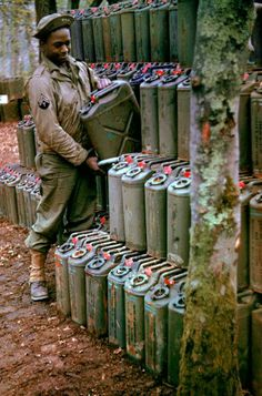 An American corporal stacks cans of gasoline in preparation for the upcoming invasion of France, Stratford-upon-Avon, England, May 1944.