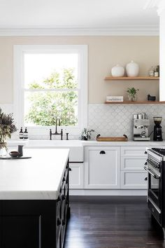 Exquisite black and white kitchen is equipped with a black center island topped with a thick honed white marble countertop and positioned beside a farmhouse sink with an oil rubbed bronze deck mount gooseneck faucet fixed beneath a window framed by cream upper walls and Tabarka Studio Artisan Terracotta Fan Tiles.