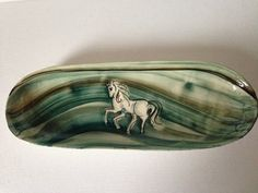 Vintage hand painted long serving/presentation platter.  Hand painted in wonderful waves of blues and greens to the base and finished with a beautiful figure of a white horse.  Signed by the artist.  This gorgeous piece would make a lovely a garlic bread, sandwich, petit-fours, hors doeuvres, sweet or nuts dish or as a stand alone piece of home decor.  The underside is plain with four little feet for the platter to sit on.  It is slightly tapered.  A fabulous gift for a horse lover who e...