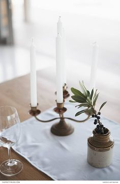 Minimalistic table setting with white candles and brass candle holders and just a touch of greenery