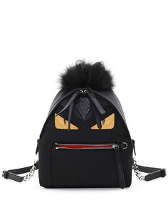 Fendi mini monster backpack in calfskin and faux leather (polyester/nylon). Dyed fox fur (Finland) and dyed goat fur (China) mohawk at top. Snakeskin detail at top center. Monster face motif with snak