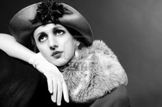 Retro styled fashion portrait of a young woman in hat. Clothing and make-up in vintage 1920s style