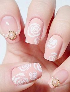 We can't decide what we love more about this nail art—the pearl decals or the intricately painted white roses on a pretty pink base.