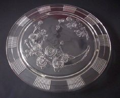 This Federal Glass cake plate was made in the 1930s.  It has a clear smooth glass top with a Rose of Sharon pattern pressed on the underside of the plate.  This footed plate has sections of a pressed ribbing pattern that encircle the rim. <br /><br />Measures:   approx. 11 3/8 inches diameter<br ...
