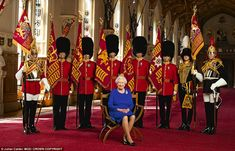 The Queen sits on the chair designed for her to use at the Birthday Parade, flanked by representatives of the seven regiments of the Household Division, of which she is Colonel-in-Chief, and the King's Troop, Royal Horse Artillery, of which she is Captain General. All carry standards except the King's Troop (second right) because the Royal Artillery have no colours but instead honour their guns