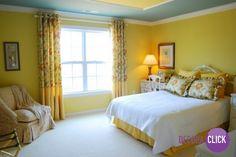 Detalhes floridos alaranjados combinam bastante com o amarelo. Neste quarto podemos ver que as capas dos travesseiros, as cortinas e a poltrona são estampadas.