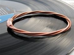 recycled piano string bracelet. this etsy seller also has bracelets, rings, etc. from guitar and bass strings. LOVE.