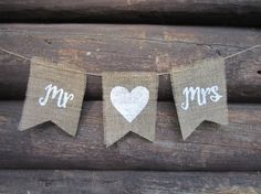 This rustic burlap banner has the words Mr and Mrs hand painted on separate flags along with a heart on its own flag in the middle. Jute twine
