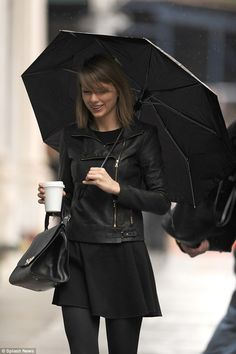 Balancing act: The superstar didn't seem to mind the rain as she gracefully carried an elegant black handbag and coffee in one arm, while balancing the umbrella in the other