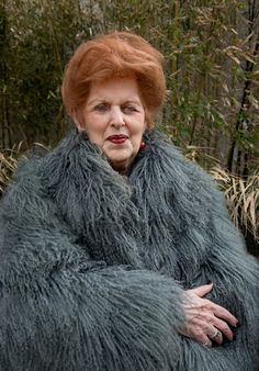 A muted blue fur coat is worn with red earrings and stacked rings