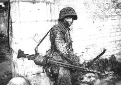 """A young German of the 12th SS """"Hitlerjugend"""" Division carries an MG 42 machine gun, nicknamed """"Hitler's Buzzsaw"""" by Allied soldiers due to its immense rate of fire of 1,200 rounds per minute. Caen, France. 1944."""