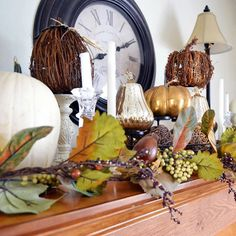 Mix of real, glass, grapevine, and papier mache pumpkins on candleholders, with garland filler.