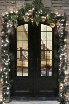 evergreen garland with white lights and silver and gold bulbs on it boardering the door