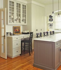 This kitchen was redone to create a family-friendly cooking and working space. A new desk and drawers opposite the island keep bills and homework in check. Glass-front cabinets above showcase bone china and goblets. Marble countertops, oil-rubbed bronze hardware, and beaded-board paneling add traditional elegance and charm.