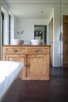 mirror wall with faucets + white vessel sinks & tub + wood vanity | via Brilliant Bathrooms ~ Cityhaüs Design