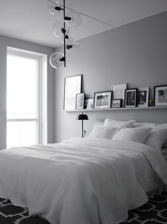 So much to love about this bedroom... the simplicity, that light fixture, the gallery picture ledge...