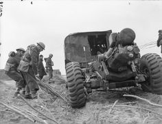 BRITISH ARMY FRANCE 1940 (F 3478)   Gunners of 3rd Medium Regiment, Royal Artillery place brushwood under the wheels of one of their 6-inch howitzers to prevent the wheels sinking into the soft ground as it is towed into position, near Calais, 30 March 1940.