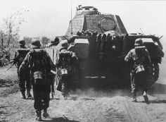 German soldiers advancing behind a Panther tank. Repined by HistorySimulation.com