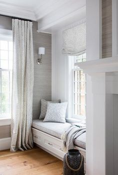 White and gray curtains hang in front of a window framed by platinum gray grasscloth wallpaper lit by nickel sconces.