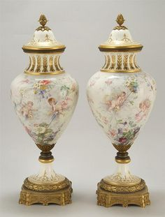 PAIR OF ORMOLU-MOUNTED SÈVRES PORCELAIN URNS Decorated with ladies and cherubs in a floral bower. Marked inside covers.