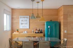 sala de jantar com parede revestida de madeira clarinha, geladeira vintage e tons neutros