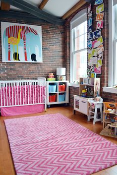 What a hip baby girl nursery! We love the exposed brick wall, and how the pink carpet just warms up the room.