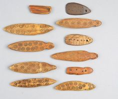 Twelve divination-bone pieces, attached on a string with point dot decoration designs; used by crocodile doctors.