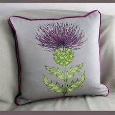 Square Purple Thistle Cushion Embroidered cushion with a purple thistle design. The cushion has a como velvet back and is filled with duck feather. Dimensions 40 cm x 40 cm
